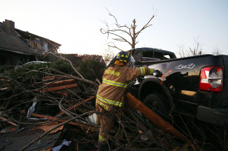 Jeremy Janssen of Mackinaw Fire Department marks a vehicle amongst the debris after a tornado struck Washington, Ill. (Photo by Tasos Katopodis/Getty Images)