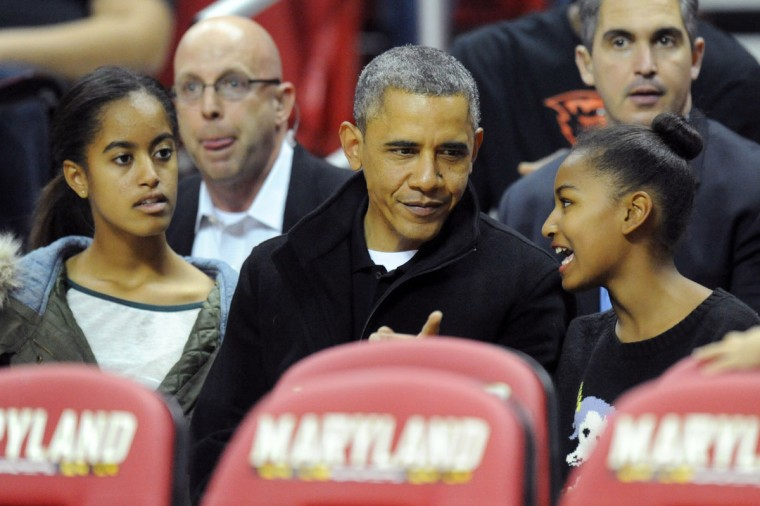 US President Barack Obama with his daughters Malia (L) and Sasha (R) in their seats before a college basketball game between the Oregon State Beavers and the Maryland Terrapins on November 17, 2013 at the Comcast Center in College Park, Maryland. (Mitchell Layton/Getty Images)