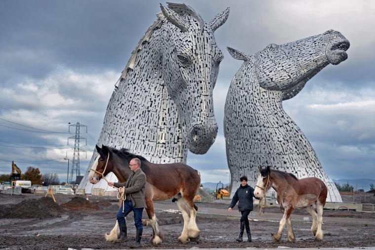 Andy Scott stands with Clydesdale Horses Duke and Baron and Donna Auchinvole during a topping out ceremony at The Kelpies on November 27, 2013 in Falkirk, Scotland. Construction work has been completed on Andy Scott's Kelpies, the world's largest pair of equine sculptures and one of the UKs tallest pieces of public art. The 30 metre tall Kelpies have cost £5million to complete and play a central role in the £43 million, 350-hectare Helix land transformational project between Falkirk and Grangemouth. (Jeff J Mitchell/Getty Images)