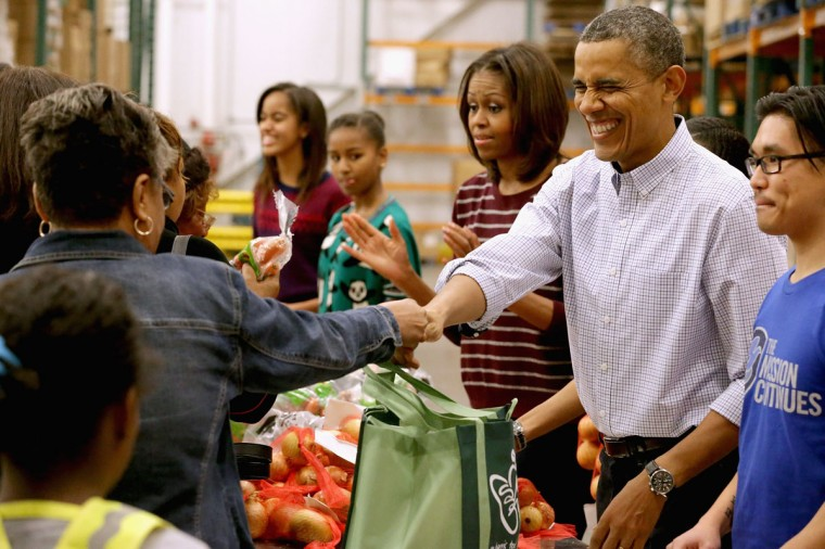 "U.S. President Barack Obama, first lady Michelle Obama, and their daughters Sasha Obama, 12, and Malia Obama, 15, help pack and sistribute bags of food to needy children and seniors at the Capital Area Food Bank November 27, 2013 in Washington, DC. According to the White House, the first family was joined by family and friends and members of The Mission Continues, ""an organization of post-9/11 veterans who are awarded community service fellowships."" (Chip Somodevilla/Getty Images)"