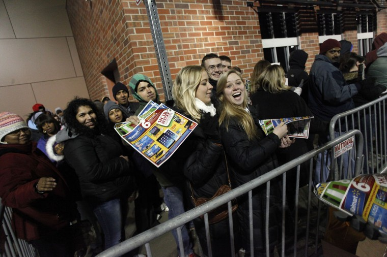 Customers receive Wal-Mart sales circulars as they wait in line to enter the store Thanksgiving day on November 28, 2013 in Troy, Michigan. Black Friday shopping began early this year with most major retailers opening their doors on Thanksgiving day as consumers took advantage of discounted prices to prepare for the holiday season. (Joshua Lott/Getty Images)