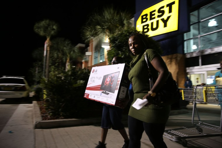 Black Friday shoppers carry away discounted items from a Best Buy store which opened its doors at 6pm on Thanksgiving Day this year on November 29, 2013 in Naples, Florida. One of the busiest days in the calendar for retailers, over a dozen US stores opened their doors to shoppers one day ahead of the famed-Black Friday shopping day.(Spencer Platt/Getty Images)