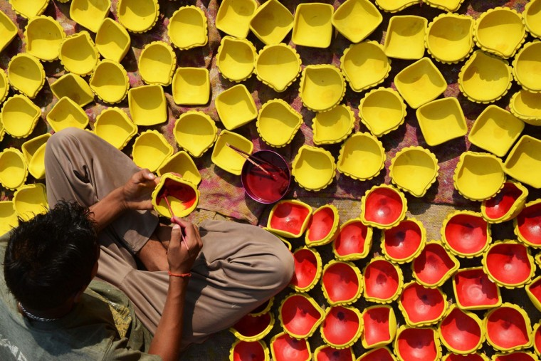 An Indian craftsman paints clay 'diyas' (earthen lamps) ahead of the Hindu festival of Diwali in Amritsar on October 29, 2013. Diwali, celebrated this year on November 3 marks the victory of good over evil and commemorates the time when Hindu God Lord Rama achieved victory over Ravana and returned to his Kingdom Ayodhya after 14 years of exile. (Narinder Nanu/AFP/Getty Images)