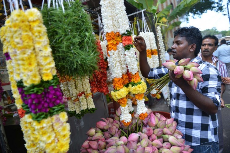 A Sri Lankan flower vendor makes a floral garland outside a Hindu temple in Colombo on November 1, 2013. Hindus throughout the world will celebrate Diwali on November 3. ( Ishara S. Kodikar/AFP/Getty Images)