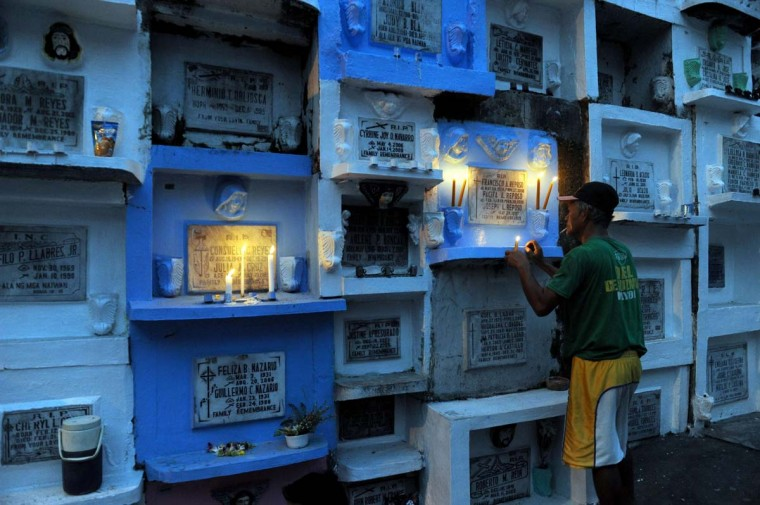 A relative lights candles at the tomb stone of a departed love one in Manila on November 1, 2013. Millions across the Catholic Philippines trooped to cemeteries to honour their dead in typically festive fashion on All Saints' Day Friday, ignoring appeals from the Church to keep the day solemn. (Jay Directo/AFP/Getty Images)