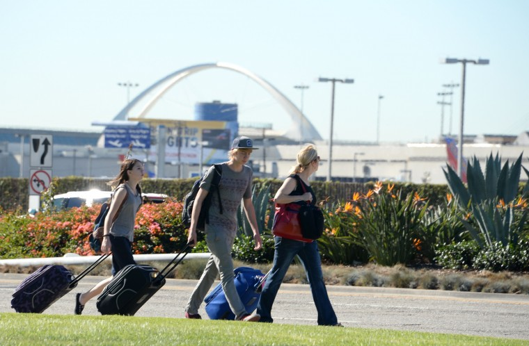 Passengers carry their bags at Los Angeles International Airport on November 1, 2013 after a gunman repotedly shot 3 people at a security checkpoint. (Robyn Beck/Getty Images)