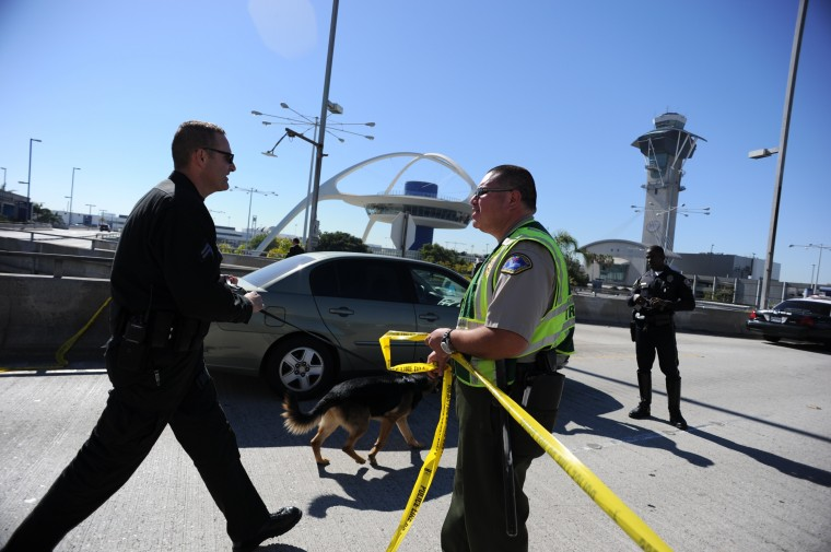 A K-9 officer (L) crosses a crime tape line on November 1, 2013 after a gunman reportedly opened fire at a security checkpointin Los Angeles International Airport. (Robyn Beck/Reuters)