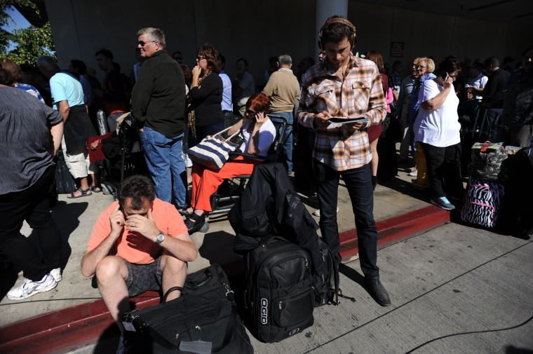 Passengers sit on the curb at Los Angeles International Airport on November 1, 2013 after a gunman reportedly opened fire at a security checkpoint. (Robyn Beck/Getty Images)