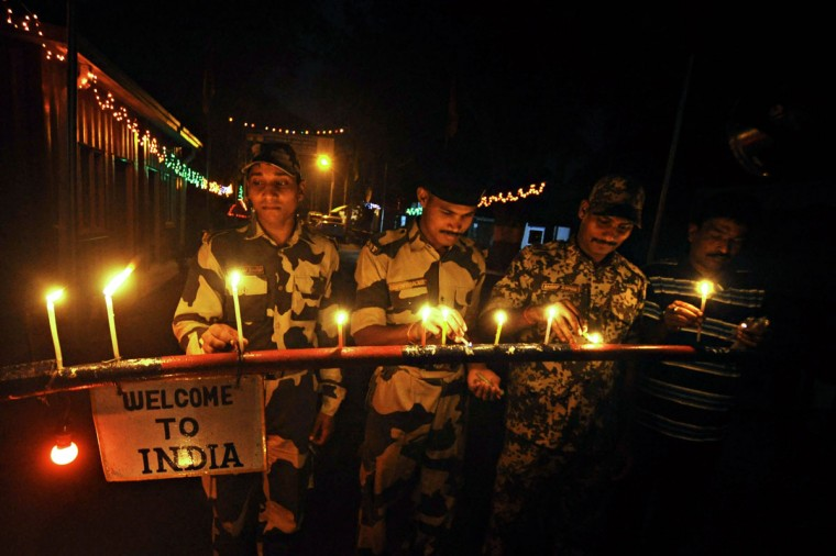 Indian Border Security Force (BSF) personnel light candles at the India-Bangladesh border crossing at Akhaura in Agartala, the capital of northeastern Indian state of Tripura, on the eve of Diwali on November 2, 2013. Diwali marks the homecoming of the Hindu god Lord Ram after vanquishing the demon king Ravana and symbolises taking people from darkness to light and the victory of good over evil. (Arindam Deyar/AFP/Getty Images)