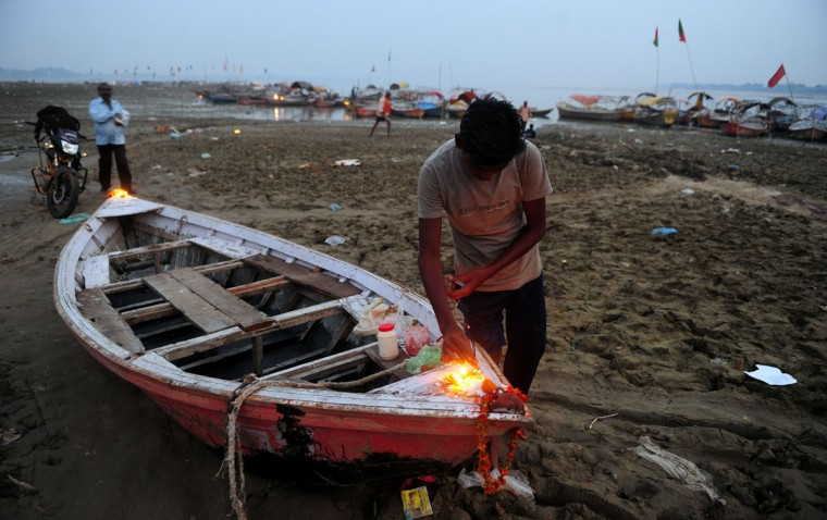 An Indian boatman lights earthen lamps placed on his boat during Diwali celebrations in Allahabad on November 3, 2013. Diwali marks the homecoming of the Hindu god Lord Ram after vanquishing the demon king Ravana and symbolises taking people from darkness to light and the victory of good over evil. (Sanjay Kanokia/AFP/Getty Images)