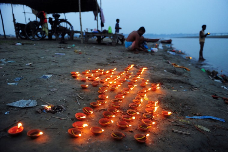 Earthen lamps are lit at the Sangam at dusk during Diwali celebrations in Allahabad on November 3, 2013. Diwali marks the homecoming of the Hindu god Lord Ram after vanquishing the demon king Ravana and symbolises taking people from darkness to light and the victory of good over evil. (Sanjay Kanojia/AFP/Getty Images)