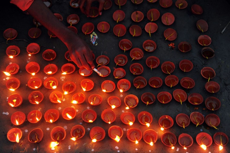 An Indian reveller lights earthen lamps during Diwali celebrations in Allahabad on November 3, 2013. Diwali marks the homecoming of the Hindu god Lord Ram after vanquishing the demon king Ravana and symbolises taking people from darkness to light and the victory of good over evil. (Sanjay Kanojia/AFP/Getty Images)