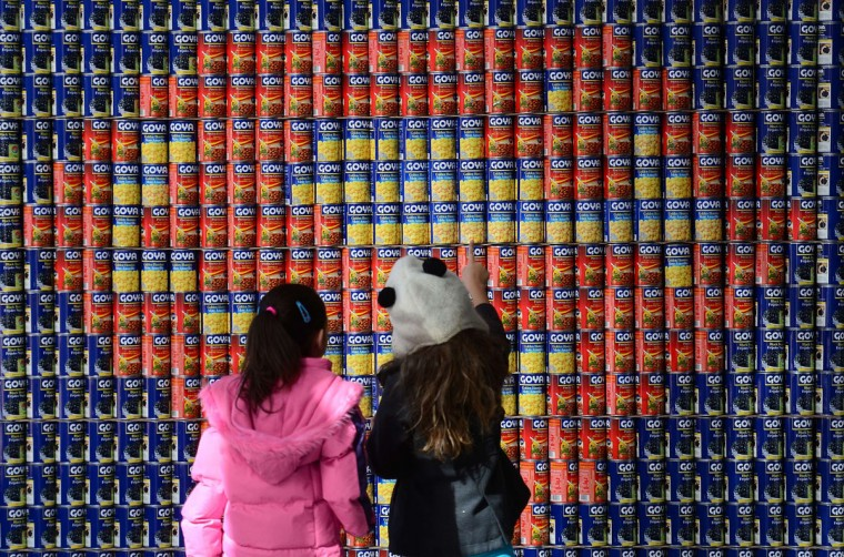 "School children look at a Superman logo made out of food cans during the 21st annual ""Canstruction"" exhibition and food drive in New York. The exhibition features sculptures made entirely of unopened canned food that will be donated to City Harvest and distributed to some 400 soup kitchens and food pantries throughout the city. (MANUEL DUNAND / AFP/Getty Images)"