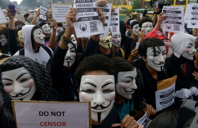 Protesters wearing Guy Fawkes masks display placards during a rally outside the House of Representatives in suburban Quezon city, north of Manila on November 5, 2013. Some 100 masked members of the hacking group Anonymous Philippines marched on parliament on November 5, denouncing corruption and pledging more cyber attacks, a week after 30 government websites were paralyzed. (Jay Directo/AFP/Getty Images)