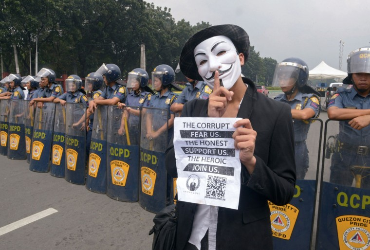 Riot police block protesters wearing Guy Fawkes masks during a rally outside the House of Representatives in suburban Quezon city, north of Manila on November 5, 2013. Some 100 masked members of the hacking group Anonymous Philippines marched on parliament on November 5, denouncing corruption and pledging more cyber attacks, a week after 30 government websites were paralysed. (Jay Directo/AFP/Getty Images)