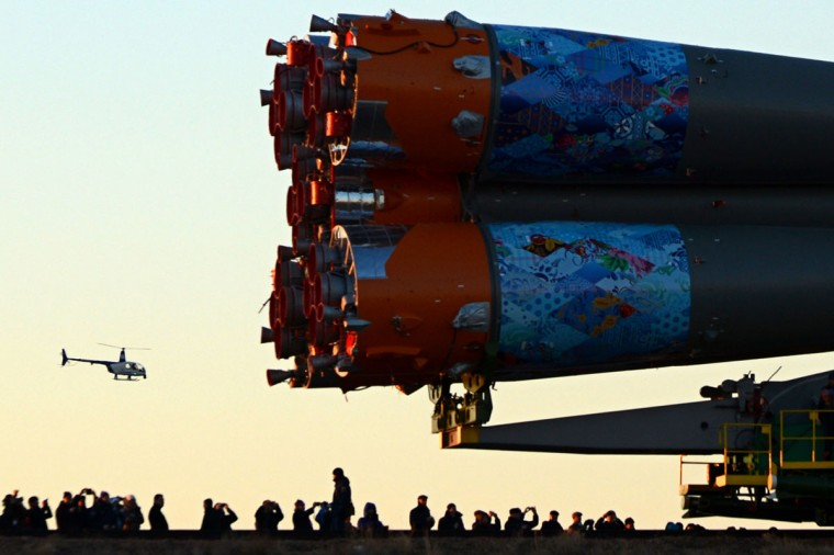 The Soyuz-FG launch vehicle with Soyuz TMA-11M spacecraft of the International Space Station (ISS) Expedition 39 aboard (partly seen right) is transported to a launch pad in the Russian-leased Baikonur cosmodrome in Kazakhstan. (KIRILL KUDRYAVTSEV / AFP/Getty Images)