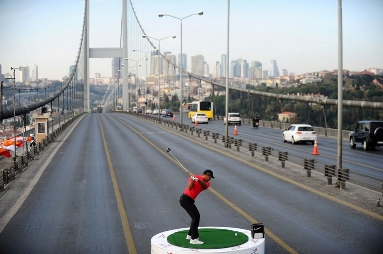 Tiger Woods hits a ball as he poses during an event to promote the upcoming Turkish Airlines Open golf tournament, on the Bosphorus Bridge that links the city's European and Asian sides, in Istanbul. (BULENT KILIC / AFP/Getty Images)
