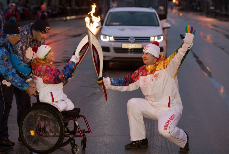 A handout picture taken during the Sochi 2014 Winter Olympic torch relay and released by the Sochi 2014 Winter Olympics Organizing Committee shows torchbearers, Maria Iovleva, a Russian biathlete and cross-country skier representing Russia at the 2010 Winter Paralympics, and Ivan Volzhanin 'kissing' with their torches to pass the Olympic flame in Syktyvkar. (AFP/Getty Images)