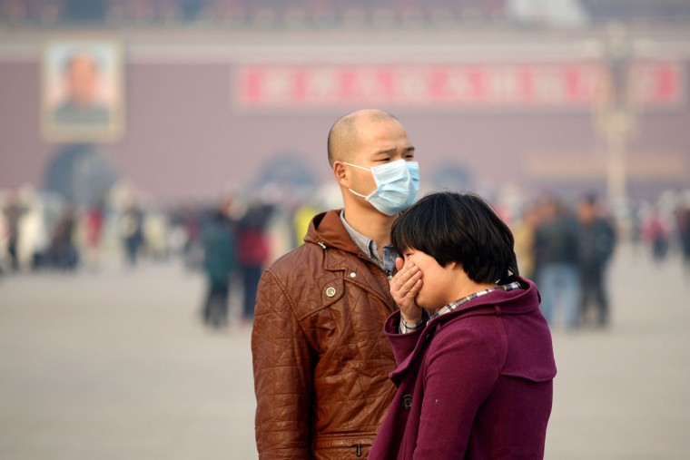 A man wears a face mask as another visitor covers her mouth during a visit to Tiananmen Square in Beijing. China's top negotiator at international climate talks said on November 5 that air pollution in his own country -- the world's biggest carbon emitter -- is harming its citizens. (WANG ZHAO / AFP/Getty Images)