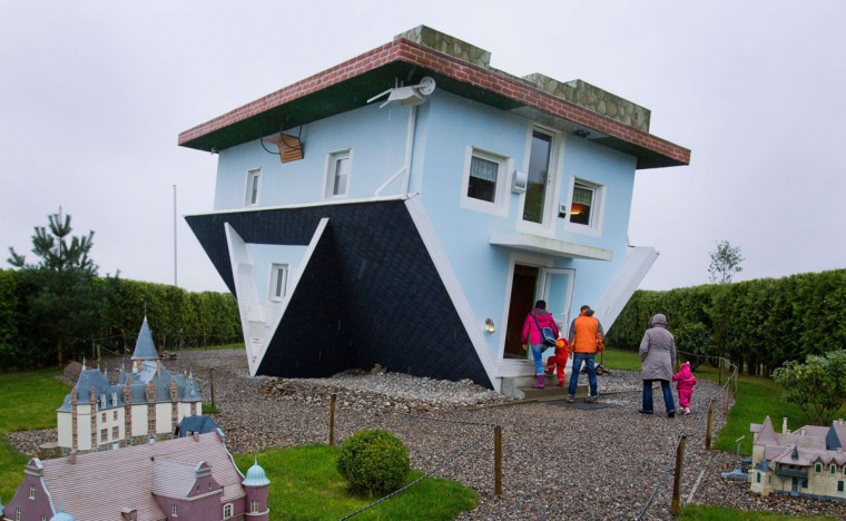 Visitors enter a house standing upside down in Trassenheide on the Baltic Sea island of Usedom, northeastern Germany. The house was already constructed in 2008 by two Polish initiators, who also designed the house's interior upside down. (JENS BUETTNER / AFP/Getty Images)