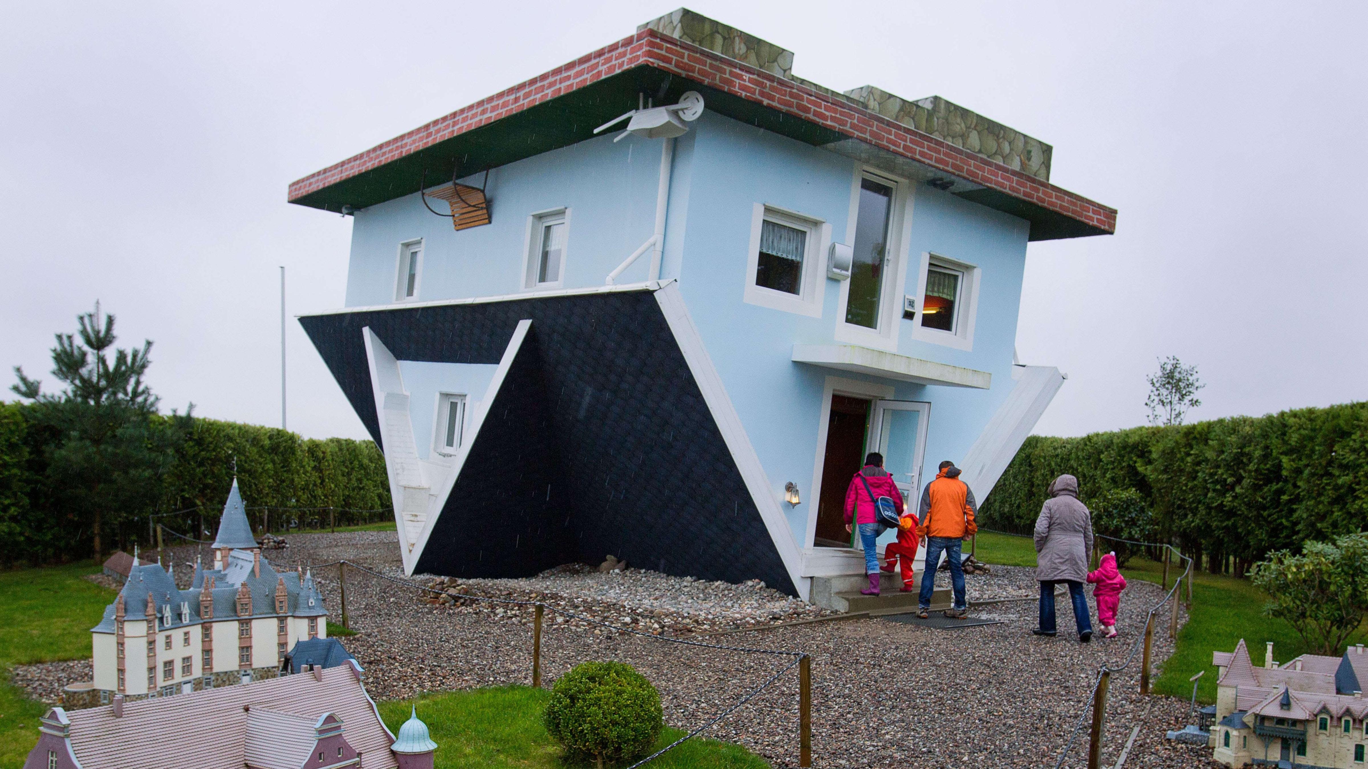 Nov. 5 Photo Brief: An upside-down house, volcano in Sumatra, torchbearers in Sochi