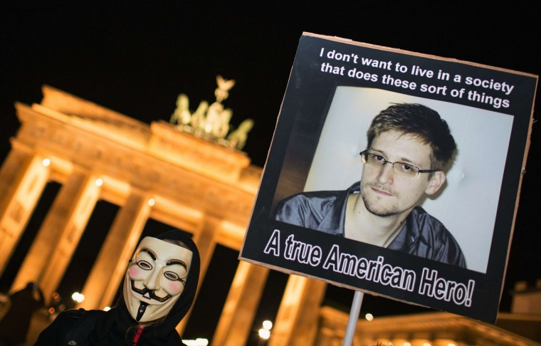"A supporter of the Anonymous group wearing a Guy Fawkes mask holds up a placard featuring a photo of US intelligence leaker Edward Snowden and reads ""A true American Hero!"" during a rally in front of Berlin's landmark Brandenburg Gate on November 5, 2013. The ""One million masks"" protests organized by the Anonymous group are taking place on Guy Fawkes Day all over the world. (Florian Schuh/AFP/Getty Images)"