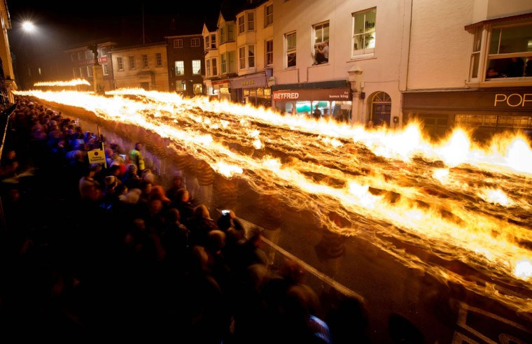 Crowds gather to watch as Bonfire societies parade through the streets during the Bonfire Night celebrations on November 5, 2013 in Lewes, Sussex in England. Bonfire Night is related to the ancient festival of Samhain, the Celtic New Year. Processions held across the South of England culminate in Lewes on November 5, commemorating the memory of the seventeen Protestant martyrs. Thousands of people attend the parade as Bonfire Societies parade through the narrow streets until the evening comes to an end with the burning of an effigy, or 'guy,' usually representing Guy Fawkes, who died in 1605 after an unsuccessful attempt to blow up The Houses of Parliament. (Leon Neal/AFP/Getty Images)