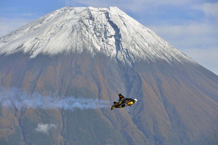 """This handout picture taken near Fujinomiya in Shizuoka prefecture on October 30, 2013 and released on November 6, 2013 shows Swiss pilot Yves Rossy, or """"Jetman"""", flying near Mount Fuji. Swiss aviator Yves """"Jetman"""" Rossy, whose jet-engine powered wings have taken him over some of the world's most awe-inspiring places, has added another -- Japan's Mount Fuji. Rossy, with a 60-kilogram (132-pound) kit strapped on his back, circled the country's highest and most revered mountain nine times over one week. (Katsuhiko Tokunaga/AFP/Getty Images)"""