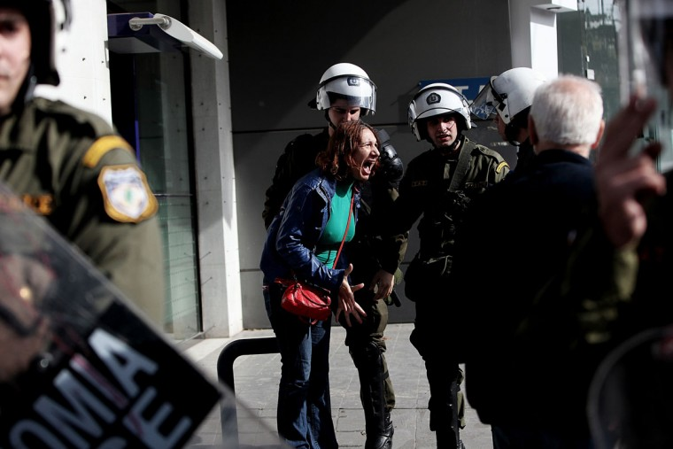 A woman argues with riot police on November 7, 2013 as she tries to pass outside the headquarters of former public broadcaster ERT in Athens. Greek riot police burst into the headquarters of former public broadcaster ERT early on November 7 and forcibly removed employees who had been occupying the site since its shock shutdown five months ago. (Angelos TzortzinisAFP/Getty Images)