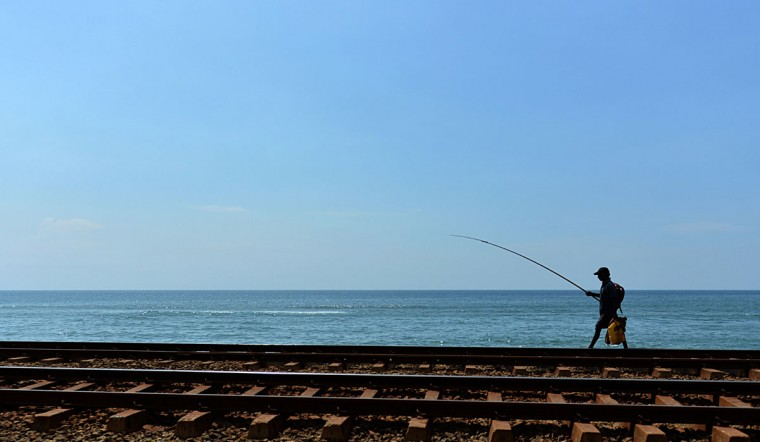 A Sri Lankan fisherman walks along a rock jetty in Colombo on November 7, 2013. The International Monetary Fund (IMF) expects growth for the current calendar year to be about 6.5 percent, a full percentage point lower than the Sri Lankan central bank's forecast of 7.5 percent. (Ishara S. Kodikara/AFP/Getty Images)