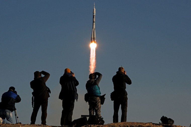 People take photographs as Russia's Soyuz TMA-11M spacecraft carrying an international crew including Japanese astronaut Koichi Wakata, Russian cosmonaut Mikhail Tyurin and US astronaut Rick Mastracchio and an unlit Olympic torch for the 2014 Winter Games in Sochi aboard blasts off from the Russian leased Kazakh Baikonur cosmodrome on November 7, 2013. Two Russian astronauts will take the unlit torch on a space walk on November 9 before it returns back to Earth on November 11. (Kirill Kudryavts/AFP/Getty Images)