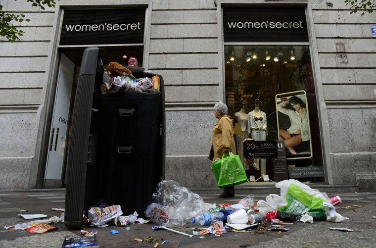 A woman walks past a garbage bin in the center of Madrid on November 7, 2013, on the third day of strike by street-sweepers against layoffs and salary cuts. Public bins overflowed with drinks cans and cigarette ends and central squares such as the Puerta del Sol were strewn with waste paper as the open-ended strike entered its third day. (Pierre-Philippe Marcou/AFP/Getty Images)
