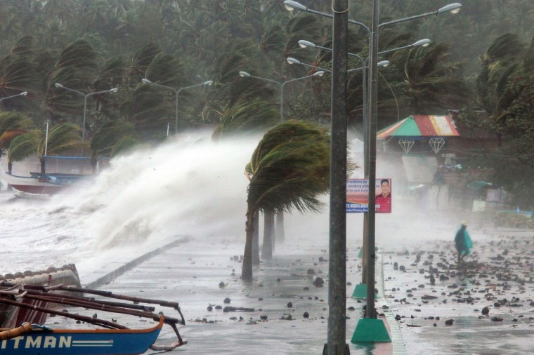 A resident walks past high waves pounding the sea wall amidst strong winds as Typhoon Haiyan hit the city of Legaspi, Albay province, south of Manila on Nov. 8, 2013. (AFP/Getty Images/Charism Sayat)