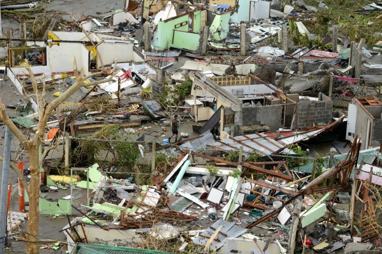 A man walks among debris of destroyed houses in the aftermath of Super Typhoon Haiyan in Tacloban, eastern island of Leyte on November 9, 2013. One of the strongest typhoons on record killed more than 100 people as savage winds and giant waves flattened communities across the Philippines, authorities said on November 9 while corpses lay amid the devastation. (Noel Celis/AFP/Getty Images)