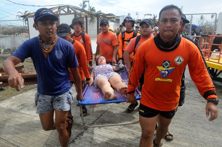 Rescue workers carry a woman about to give birth at a makeshift Department of Health (DOH) medical center at the Tacloban airport in the aftermath of Super Typhoon Haiyan in Tacloban, eastern island of Leyte on November 9, 2013. One of the strongest typhoons on record killed more than 100 people as savage winds and giant waves flattened communities across the Philippines, authorities said on November 9 while corpses lay amid the devastation. (Noel Celis/AFP/Getty Images)