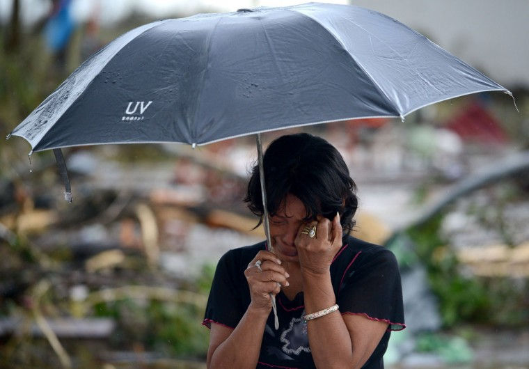 A woman mourns in front of her husband's dead body in a street of Tacloban, eastern island of Leyte on November 10, 2013. The Pentagon said it was providing the Philippines with naval and aviation resources in the wake of a devastating typhoon. The U.N. said that it expected the provisional death toll from super typhoon Haiyan to rise and is sending emergency supplies to the stricken country. (Noel Celis/AFP/Getty Images)