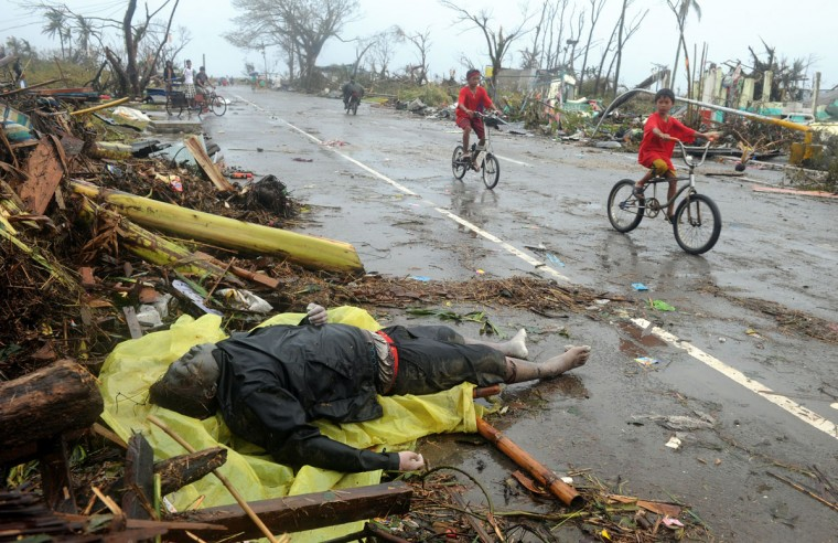 Children cycles past a dead body on a street in Tacloban, eastern island of Leyte on November 10, 2013. A super typhoon that destroyed entire towns across the Philippines is believed to have killed more than 10,000 people, authorities said on November 10, which would make it the country's deadliest recorded natural disaster. (Noel Celis/AFP/Getty Images)