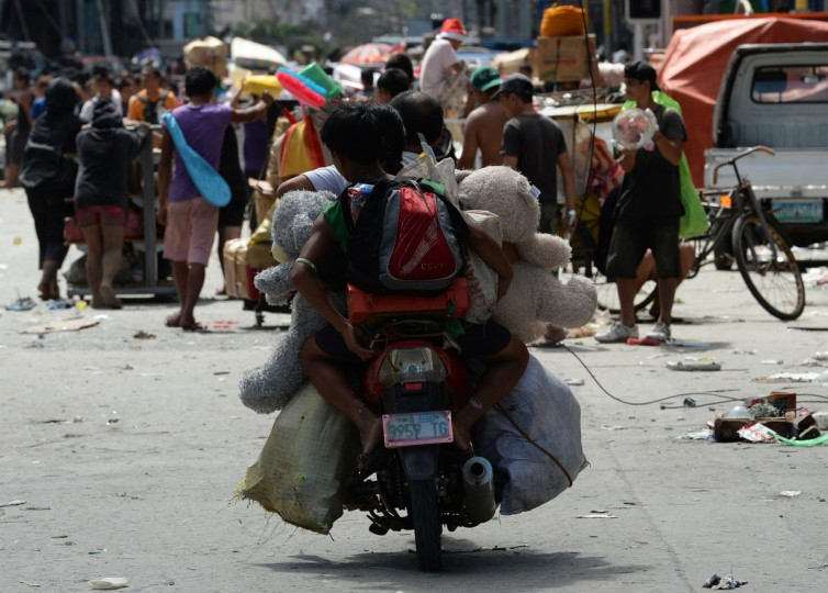 Residents carry their looted goods in Tacloban City, Leyte province, central Philippines on November 10, 2013, days after devastating Typhoon Haiyan hit the city on November 8. The death toll from a super typhoon that decimated entire towns in the Philippines could soar well over 10,000, authorities warned on November 10, making it the country's worst recorded natural disaster. (Ted Aljibe/AFP/Getty Images)