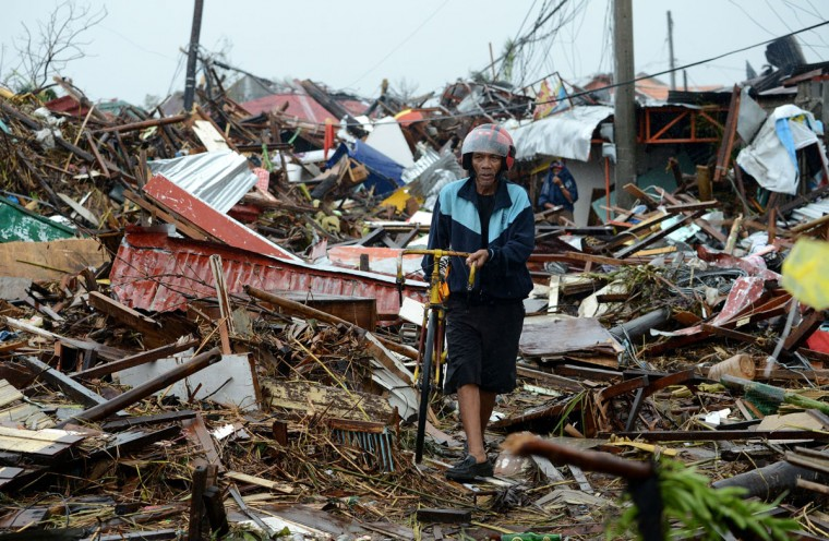 A man walks past destroyed houses in Tacloban, eastern island of Leyte on November 10, 2013. (Noel Celis/AFP/Getty Images)