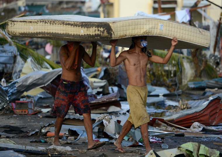 Residents carry a mattress taken from a hotel in Palo, eastern island of Leyte on November 10, 2013. The death toll from a super typhoon that decimated entire towns in the Philippines could soar well over 10,000, authorities warned on November 10, making it the country's worst recorded natural disaster. (NoeL Celis/AFP/Getty Images)