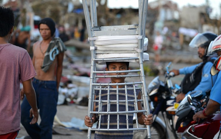 A child carries a chair taken from a hotel in Palo, eastern island of Leyte on November 10, 2013, days after devastating Super Typhoon Haiyan hit the area on November 8. The death toll from a super typhoon that decimated entire towns in the Philippines could soar well over 10,000, authorities warned on November 10, making it the country's worst recorded natural disaster. (NoeL Celis/AFP/Getty Images)