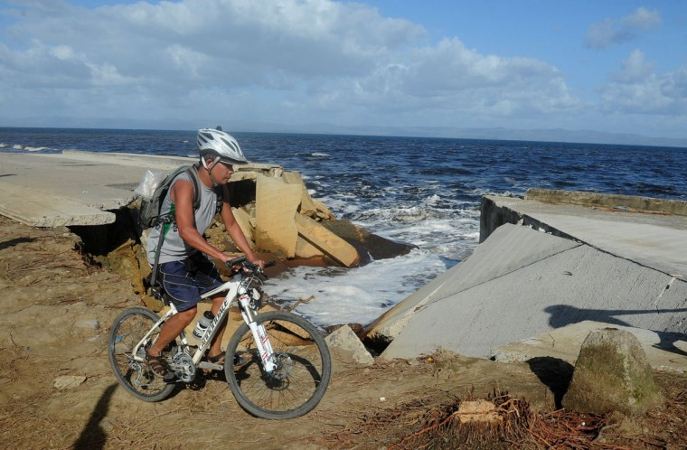 A cyclist crosses a collapsed highway caused by the storm surge in Palo, eastern island of Leyte on November 10, 2013, days after devastating typhoon Haiyan hit the area on November 8. The death toll from a super typhoon that decimated entire towns in the Philippines could soar well over 10,000, authorities warned on November 10, making it the country's worst recorded natural disaster. (Noel Celis/AFP/Getty Images)