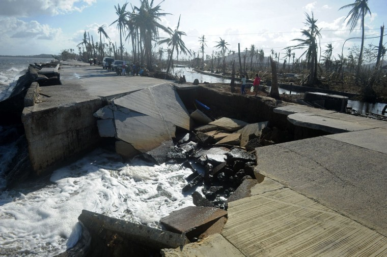 Residents cross a collapsed highway caused by the storm surge in Palo, eastern island of Leyte on November 10, 2013, days after devastating typhoon Haiyan hit the area on November 8. (Noel Celis/AFP/Getty Images)