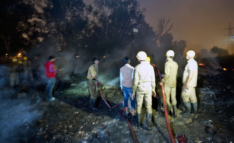 Delhi Fire Service personnel extinguish a fire in New Delhi. Slum huts were gutted in a fire which broke out in the evening near Delhi's Ghazipur mandi. (PRAKASH SINGH / AFP/Getty Images)
