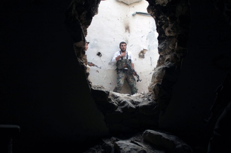 Rebel fighters hold a position in a damaged building during clashes with Syrian government forces in the northeastern city of Deir Ezzor. Syria's main opposition grouping said Monday it was willing to attend peace talks on the condition that President Bashar al-Assad transfer power and be excluded from any transition process. (AHMAD ABOUD / AFP/Getty Images)
