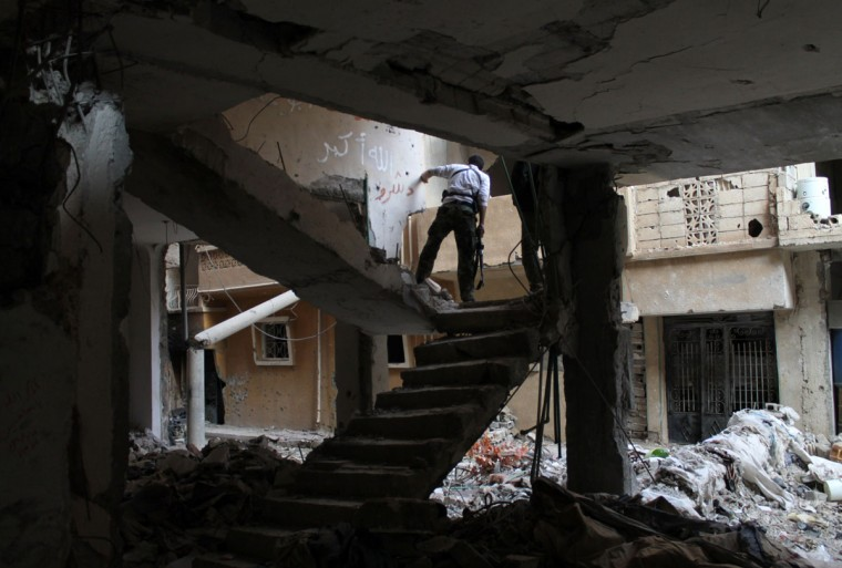 A rebel fighter holds a position in a damaged building during clashes with Syrian government forces in the northeastern city of Deir Ezzor. Syria's main opposition grouping said Monday it was willing to attend peace talks on the condition that President Bashar al-Assad transfer power and be excluded from any transition process. (AHMAD ABOUD / AFP/Getty Images)