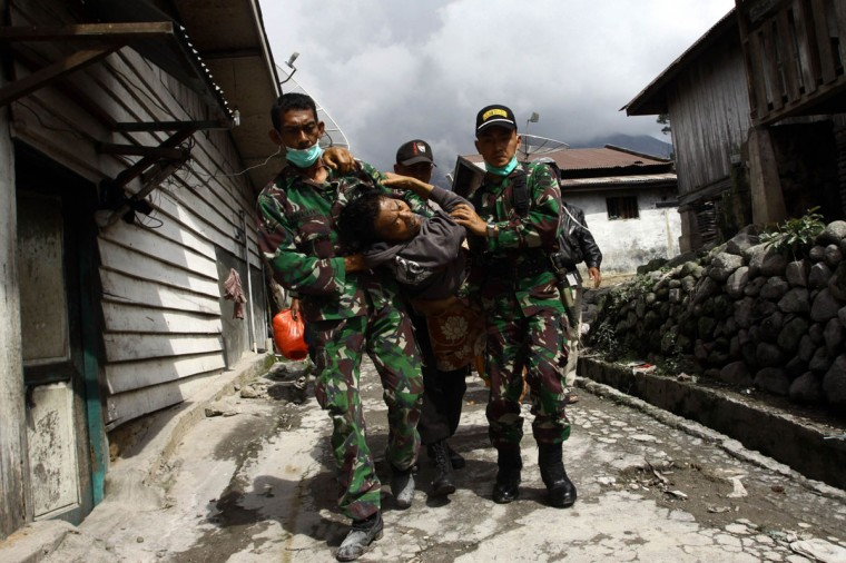 An ailing man is evacuated by Indonesian military personnel as villagers flee their homes to a shelter, at the Guru Kinayan village in Karo. More than 5,000 people have fled their homes since a volcano in western Indonesia erupted early this month, an official said. (KHARISMA TARIGAN / AFP/Getty Images)