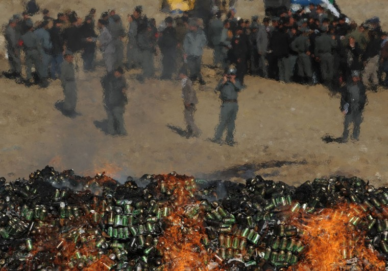 Afghan government officials and policemen watch as a cache of alcohol and drugs burn in Kabul. More than 2,000 kilograms of opium, 400 kilos of heroine, about 1,200 kilos of morphine were burned during the ceremony. (FARSHAD USYAN / AFP/Getty Images)