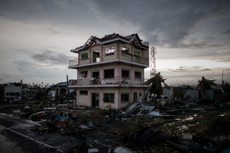 A the sun sets over a house damaged by Typhoon Haiyan outside the airport in Tacloban, on the eastern island of Leyte, after Super Typhoon Haiyan swept over the Philippines. (PHILIPPE LOPEZ / AFP/Getty Images)
