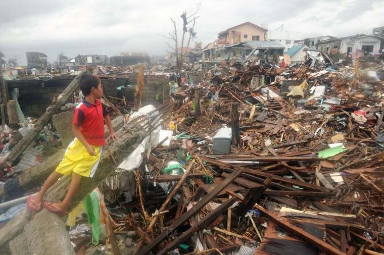 A boy looks at the debris of destroyed houses in Tacloban, on the eastern island of Leyte, after Super Typhoon Haiyan, the most powerful storm in the world this year, hit the Philippines. (NOEL CELIS / AFP/Getty Images)
